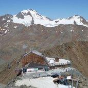 1392736396D-0728-grawand-gipfelkreuz-blick-auf-seilbahnstation-gletscherbahn-dahinter-weisskugel.jpg